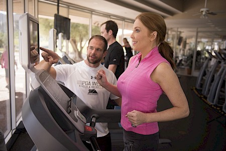Personal trainer working with client in gym
